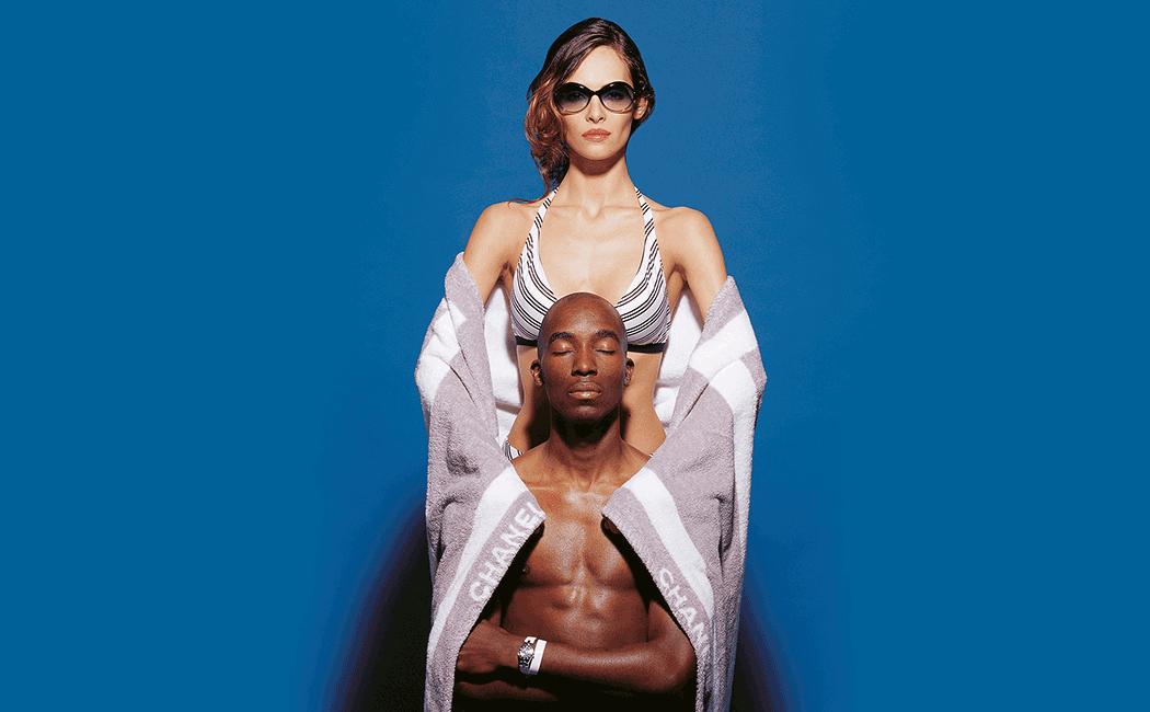 VONsociety: Nachhaltige Sommer Style, weißes weibliches Model steht vor blauem Hintergrund. Sie trägt ein blau-weiß gestreiftes Bikini-Top und eine schwarze Sonnenbrille. Vor ihr sitzt ein schwarzes männliches Model mit geschlossenen Augen. Um ihre Unterarme und seine Schultern hängt ein grau-weißes Chanel Badetuch © Paul Harris